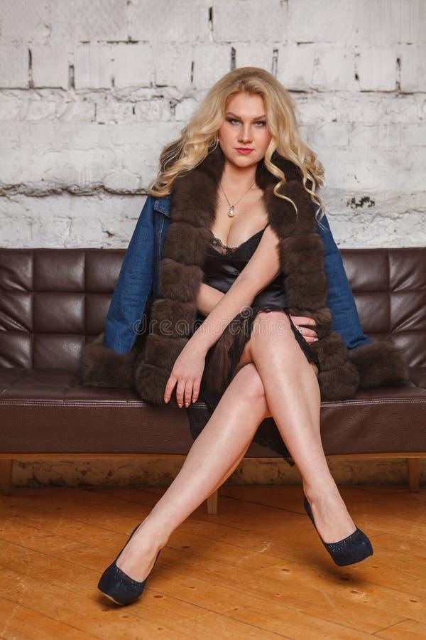 胸罩的年轻女人坐沙发 图库摄影