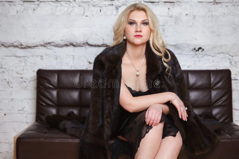 胸罩的年轻女人坐沙发 免版税库存照片