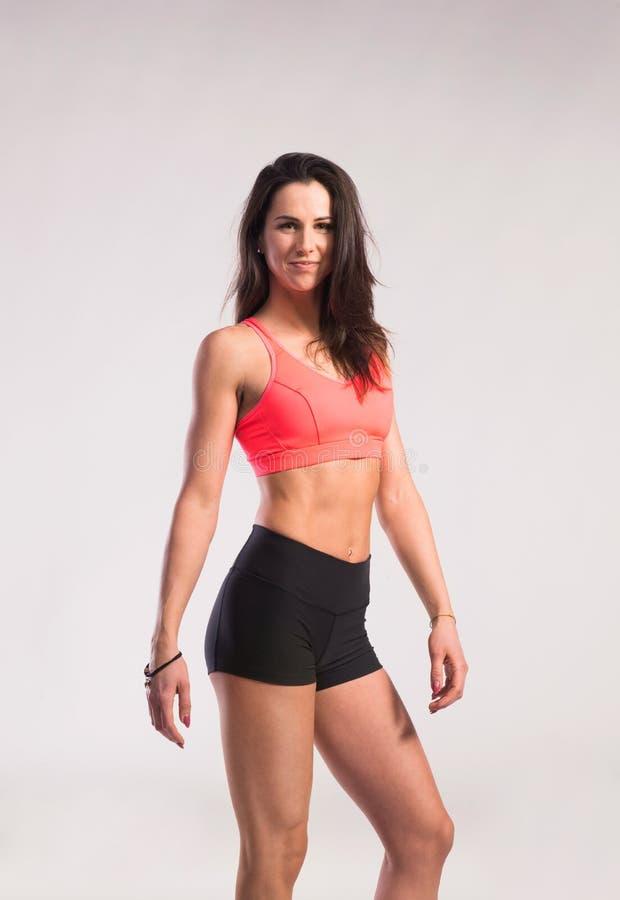 胸罩适合的短裤体育运动妇女 演播室射击,灰色背景 库存图片