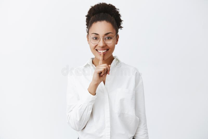能您保留秘密 玻璃和白色衬衣的快乐的兴奋的非裔美国人的女性上司,在家后来,要求 库存图片