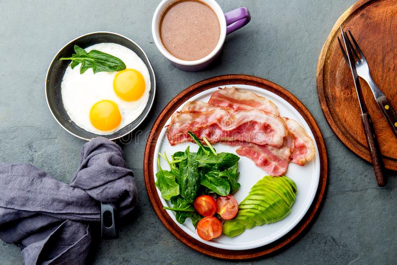 能转化为酮的饮食早餐煎蛋、烟肉和鲕梨、菠菜和防弹咖啡 低碳高脂肪早餐 库存照片