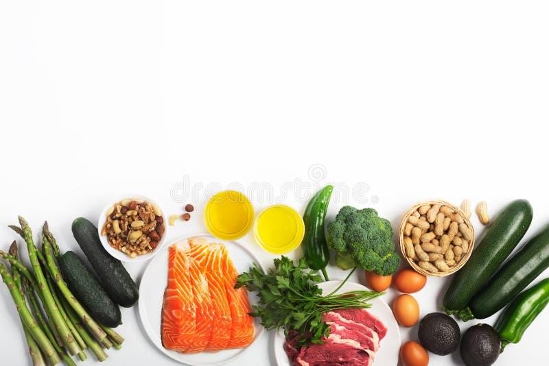 能转化为酮,keto饮食,包括菜、肉和鱼、坚果和油在白色背景与拷贝空间 库存照片