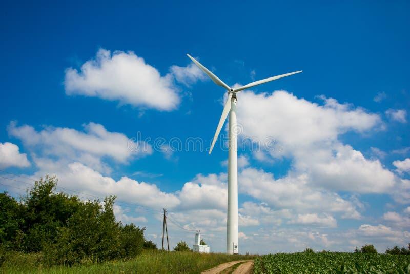 能量概念 在农田里设定的唯一风轮机在夏天 供选择的电来源 免版税库存照片