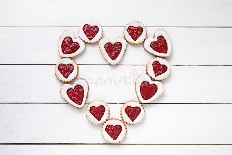 脆饼心形的曲奇饼的心脏用在白色木桌背景的果酱 库存照片