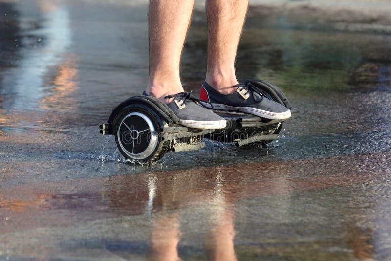 脚一个人的乘驾一segway的在湿沥青 库存图片