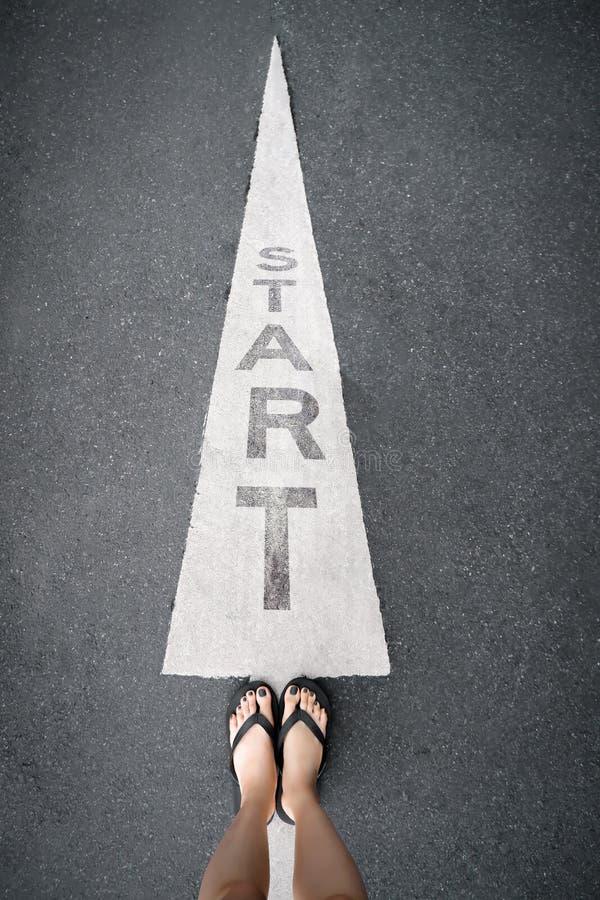 脚和箭头在起点路  在与腿和鞋子的沥青混凝土写的词开始 与灰色的妇女赤脚 免版税图库摄影