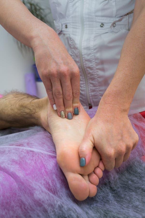 脚按摩 给腿按摩的女按摩师生理治疗师诊所的一个人 关闭 免版税库存图片