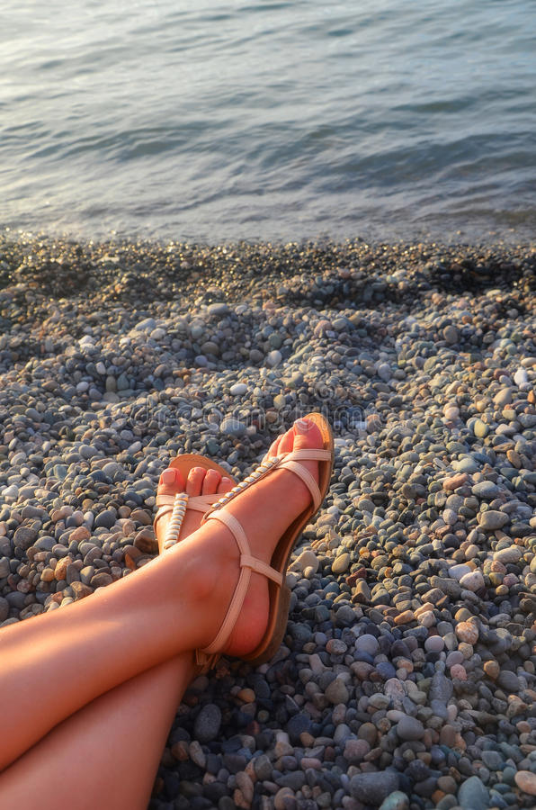 脚晒日光浴在一个石海滩的女孩-假期和旅行概念 免版税库存图片
