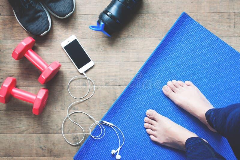 脚瑜伽妇女、智能手机、运动器材和体育鞋子Selfie在木头 免版税图库摄影
