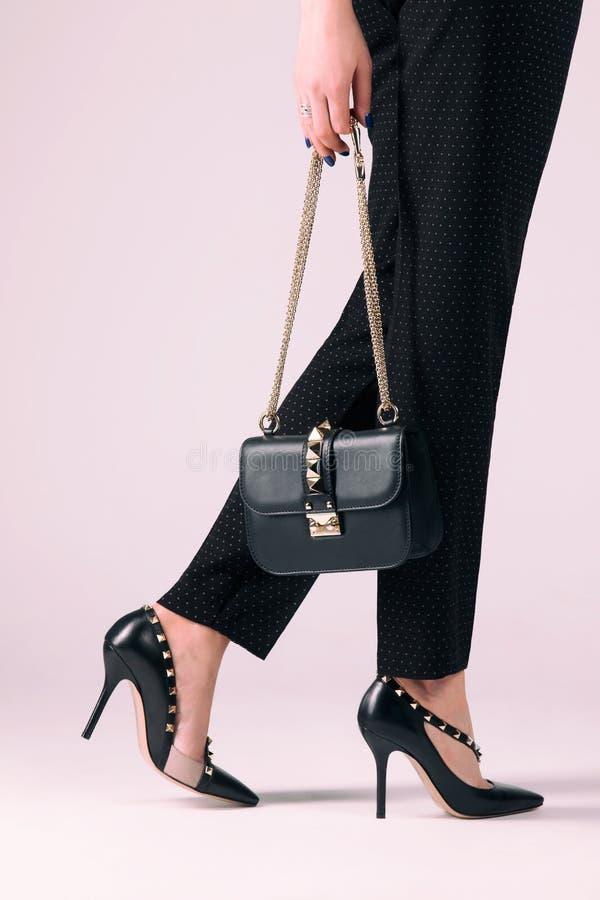 脚跟的女孩有一个袋子的在她的手上 免版税图库摄影