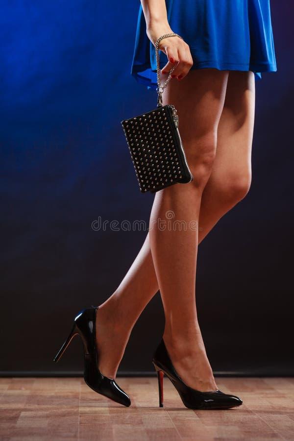 脚跟的妇女拿着提包,迪斯科俱乐部 免版税库存照片