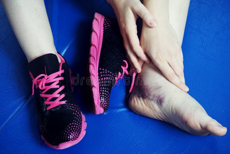 脚踝受伤,在蓝色炫耀在黑桃红色运动鞋,被扭伤的扭伤的席子 免版税库存图片