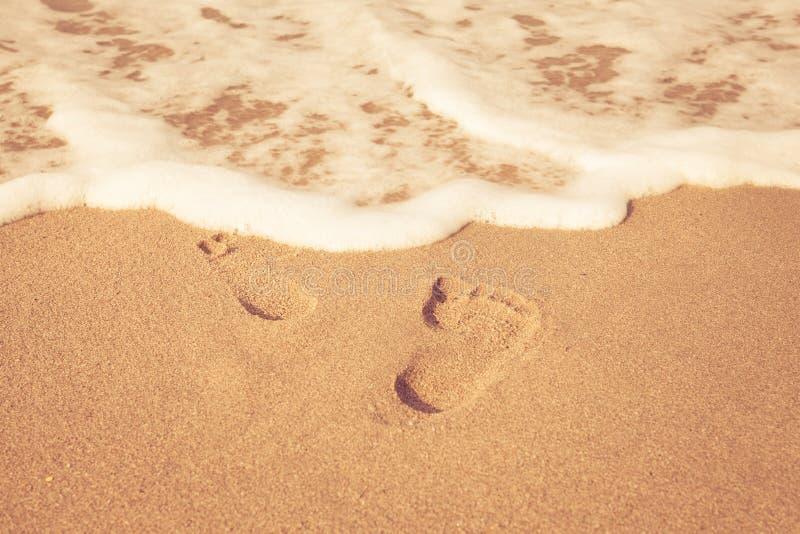 脚邮票在沙子的在与阳光的海滩早晨 库存图片