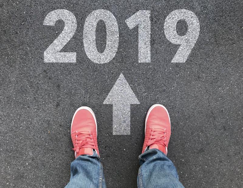脚,白色箭头和2019文本在柏油路,起动新年概念顶视图  库存图片