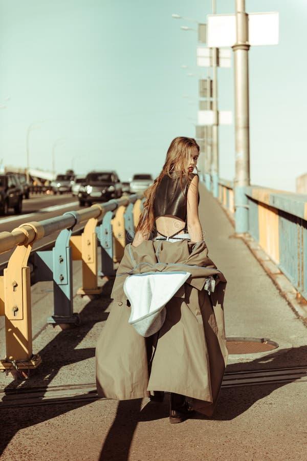 脱下灰色外套的性感的猛烈长发妇女 图库摄影