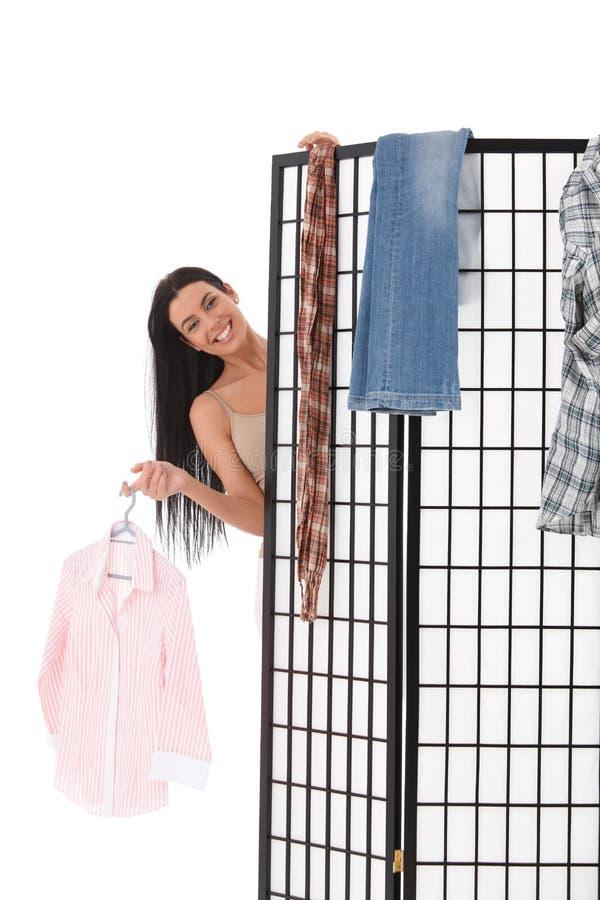 脱下衣服在穿戴的性感的女孩面板微笑之后 免版税库存照片