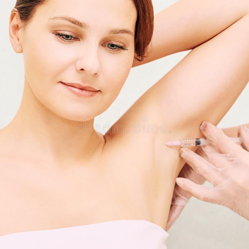 腋窝整容术射入 在化妆诊所的冒汗的治疗 妇女皮肤护理做法 Hand?? 免版税库存照片