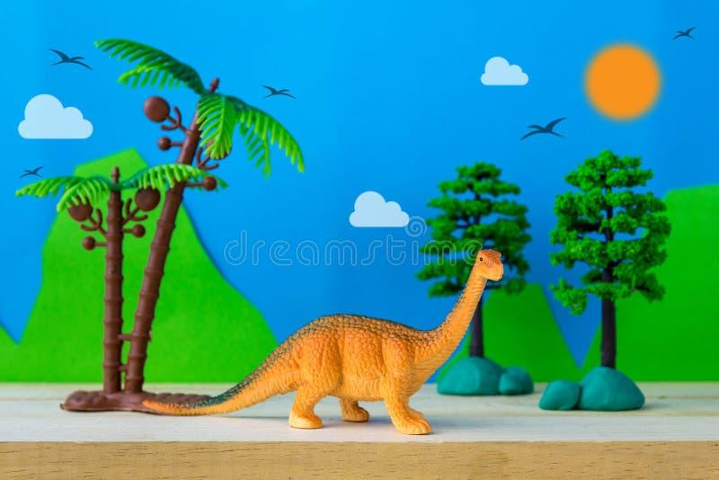 腕龙恐龙在狂放的模型背景的玩具模型 免版税库存照片