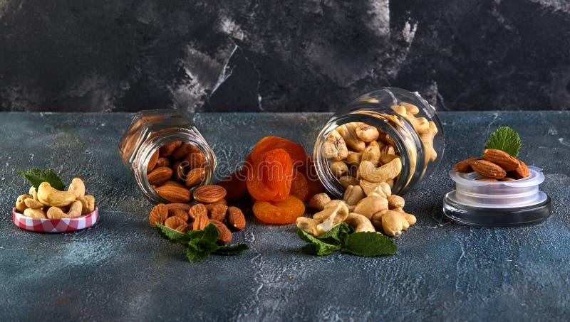 腰果杏仁溢出在透明罐头外面,杏干放在他们之间 免版税图库摄影