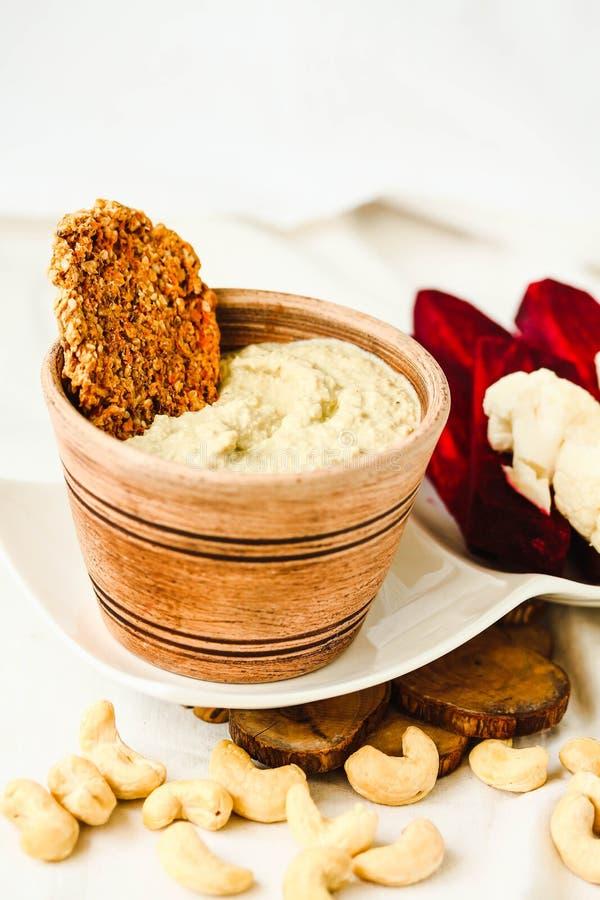 腰果调味汁,从坚果的日志免费乳酪用红萝卜薄脆饼干a 免版税库存照片