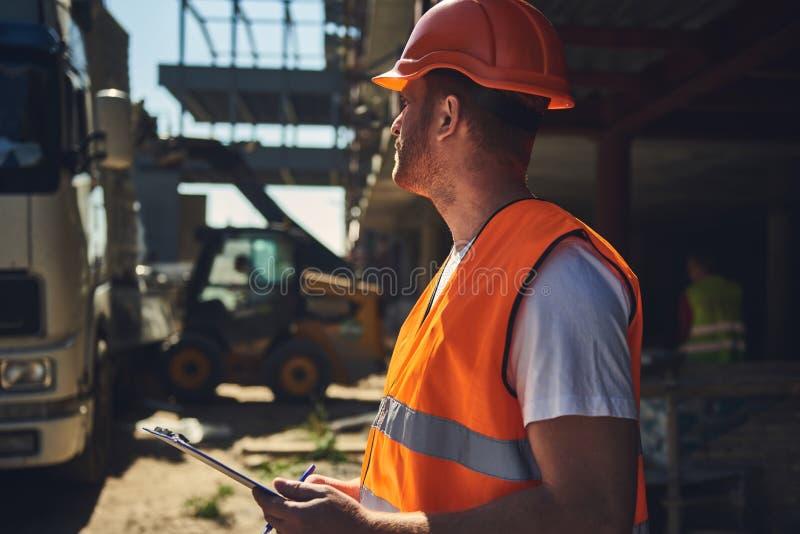 腰部与剪贴板的专业建造者身分在他的手上 库存照片