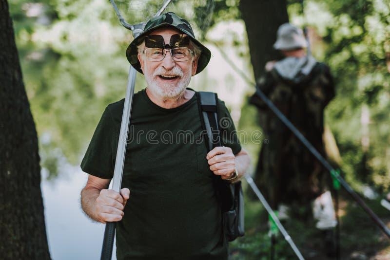 腰部享受钓鱼的一个快乐的年迈的人 免版税库存照片