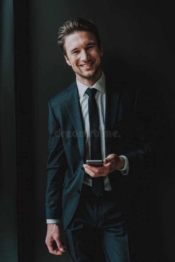 腰部微笑和拿着智能手机的快乐的典雅的人 图库摄影