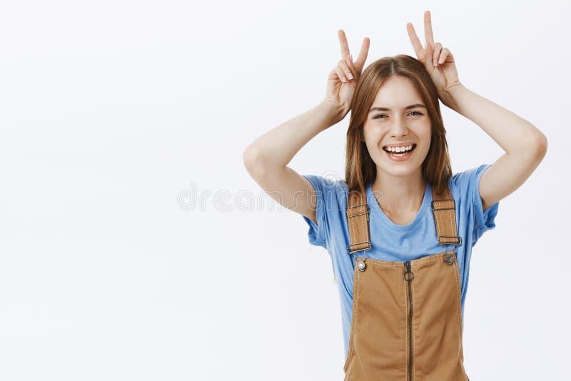 腰部微笑被射击棕色总体和蓝色T恤杉的愉快的嬉戏和感情迷人的年轻白种人的妇女和 免版税图库摄影