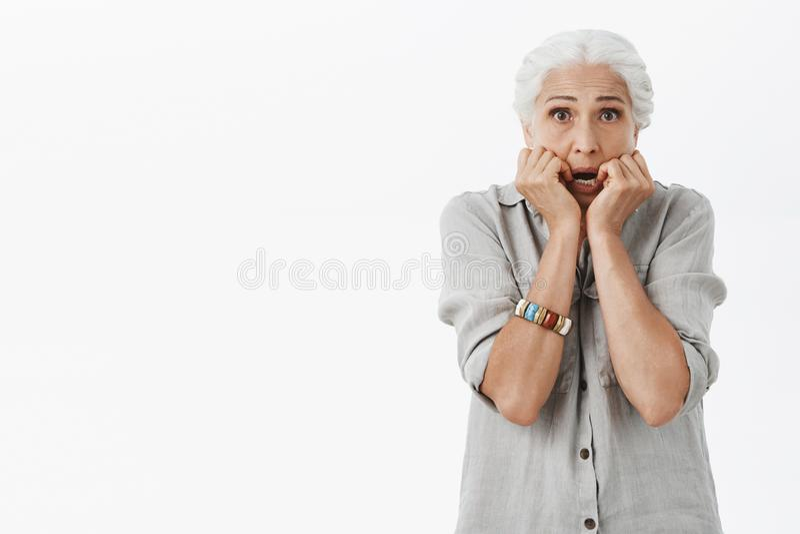 腰部感到不安全和打颤从恐惧的被射击害怕的和有关老孤独的夫人拿着棕榈在嘴附近 免版税库存图片