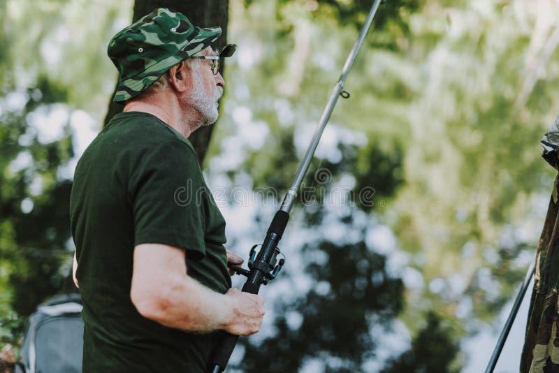 腰部拿着他的钓鱼竿的一个人 库存图片