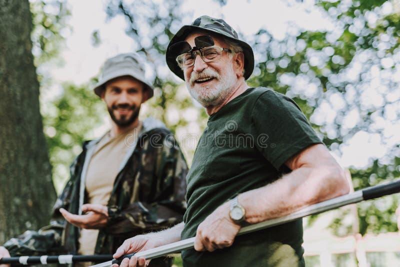 腰部拿着抢夺的一个快乐的年长人 免版税库存照片