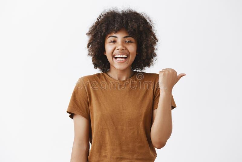 腰部指向射击了时髦的T恤杉的无忧无虑的快乐和可爱的年轻深色皮肤的女学生和 免版税图库摄影