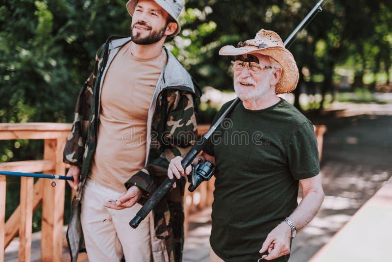 腰部有他的儿子的一个正面年长钓鱼者 免版税库存照片