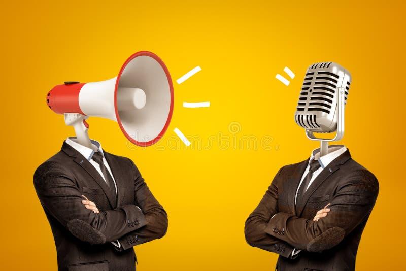 腰部深观点的两个商人站立在半轮的,胳膊折叠了,与扩音机和话筒而不是头 库存照片