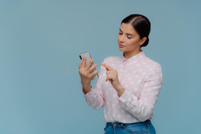 腰部突然上升了典雅的衣物的,用途手机深色头发的妇女,集中在屏幕,选择新的轨道为 免版税库存照片