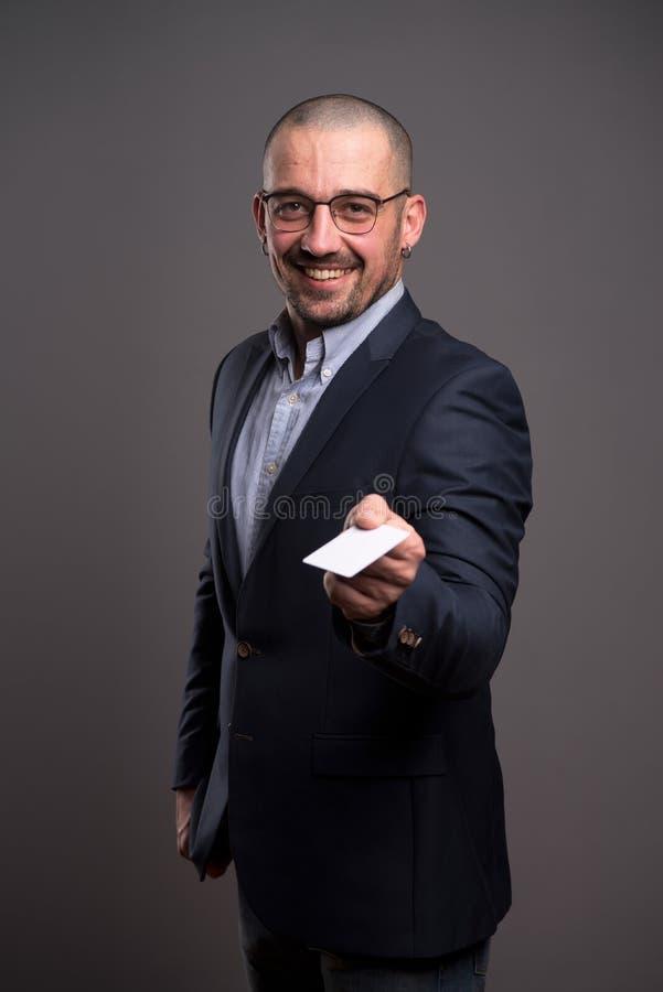 腰部给信用卡的激动的商人您 图库摄影