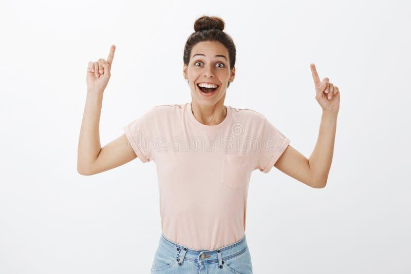 腰部被射击举手的偶然T恤杉的高兴热心惊奇的年轻愉快的女朋友指向  免版税库存图片