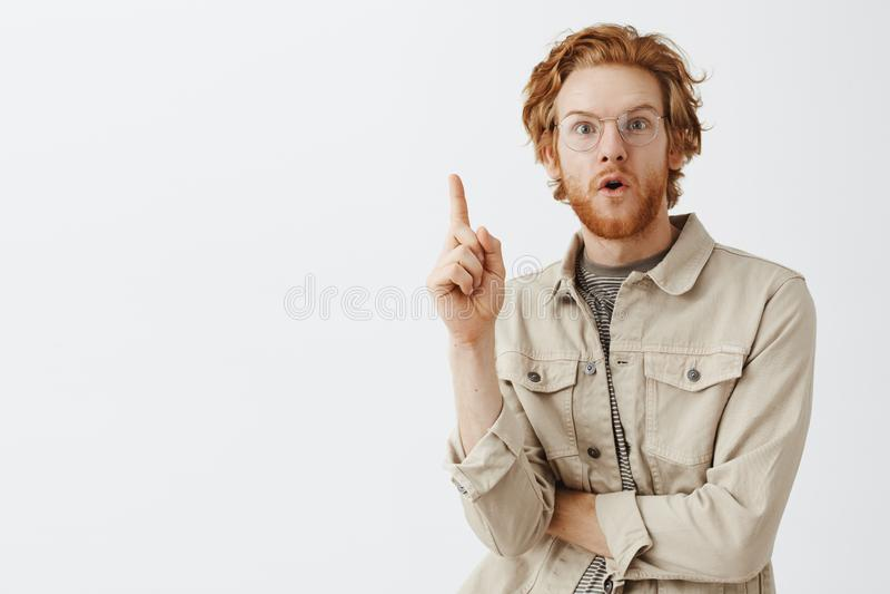 腰部被射击创造性的与波浪发的红头发人公天才和刮胡须增加站立在尤里卡姿势的巨大建议 图库摄影