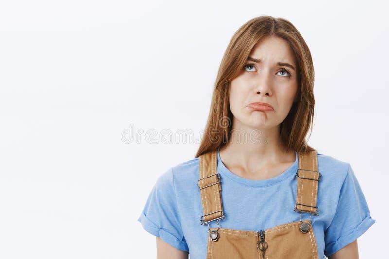 腰部被射击有棕色头发的羡慕阴沉和哀伤的逗人喜爱的女孩在做不快乐的微笑的总体和蓝色T恤杉 免版税库存照片