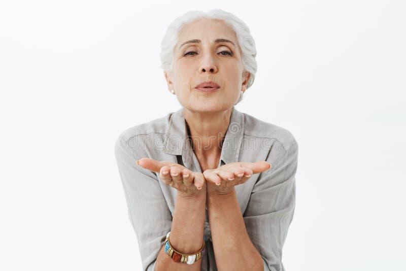 腰部被射击有灰色头发的迷人的年长妻子在弯曲往照相机的衬衣拿着棕榈在被折叠的嘴唇附近 库存照片