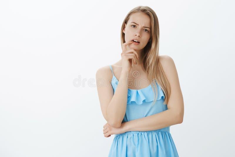 腰部被射击有金发的间隔的傻的魅力女孩在蓝色庄重装束开放嘴和接触嘴唇 免版税库存图片