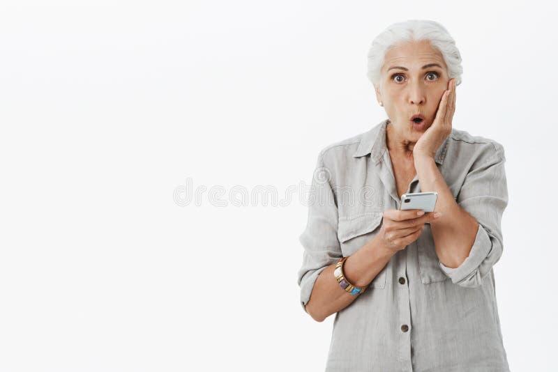 腰部被射击震惊和惊奇祖母探索的互联网折叠的嘴唇在触目惊心和惊奇藏品手上 免版税库存图片