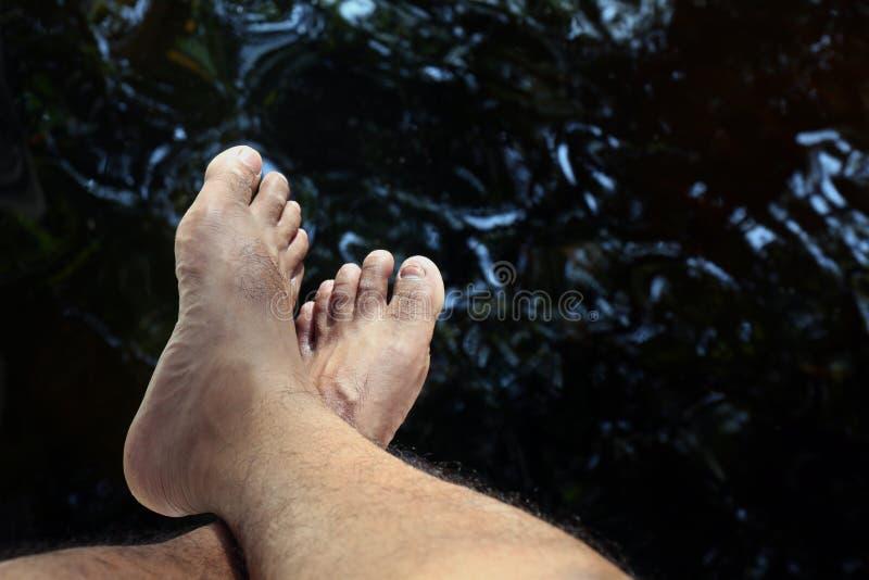 腿和结算在水表面小河为放松,旅客在浸泡的他们的腿水上坐在水中 库存图片