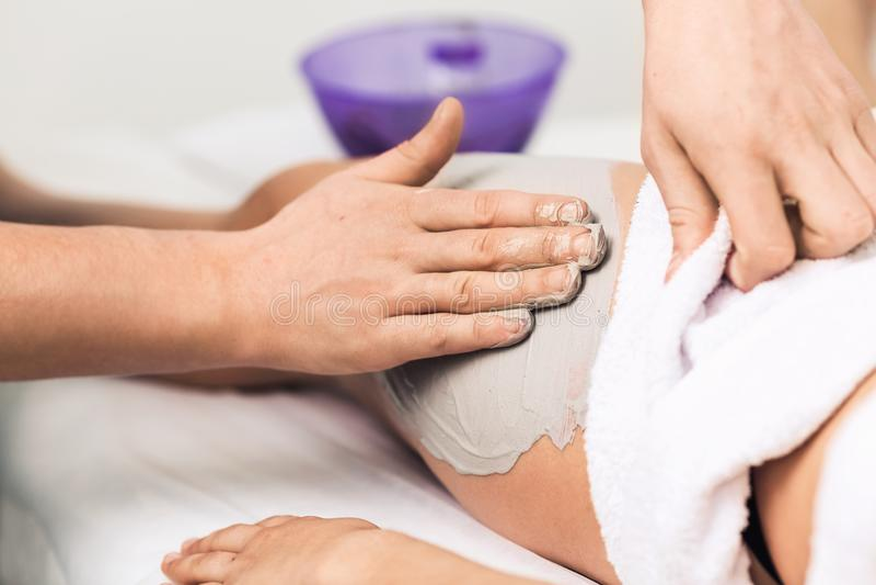 腿按摩有蓝色黏土的在温泉 化妆诊所,温泉,健康中心,医疗保健概念 免版税库存图片
