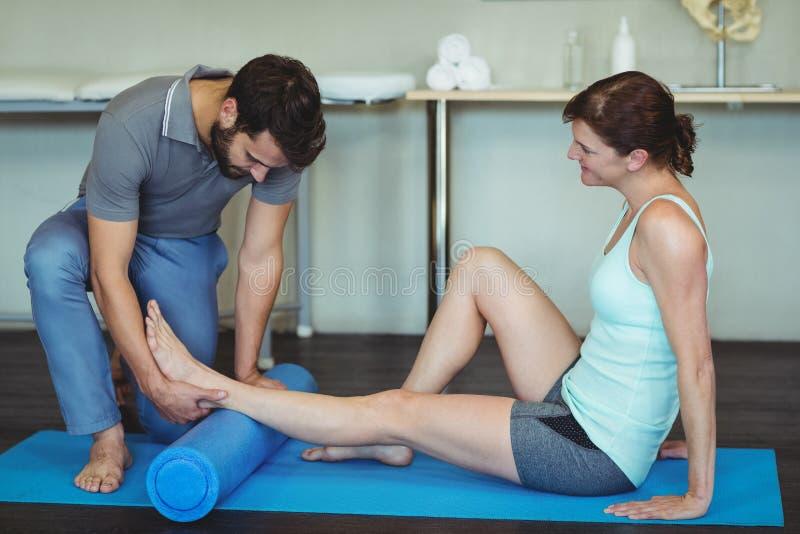 给腿按摩的生理治疗师锻炼席子的一名妇女 图库摄影