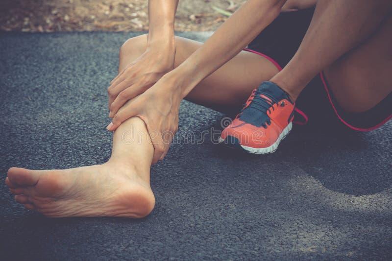 腿痛的运动妇女 运动员健身马拉松抓伤申 运动女肌肉踝 免版税库存照片
