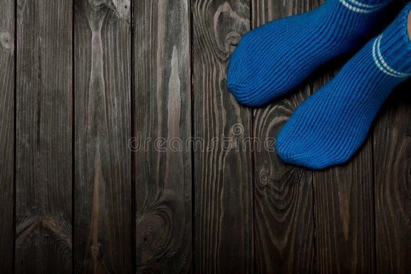 腿编织了在木黑暗的背景的蓝色羊毛袜子 库存照片