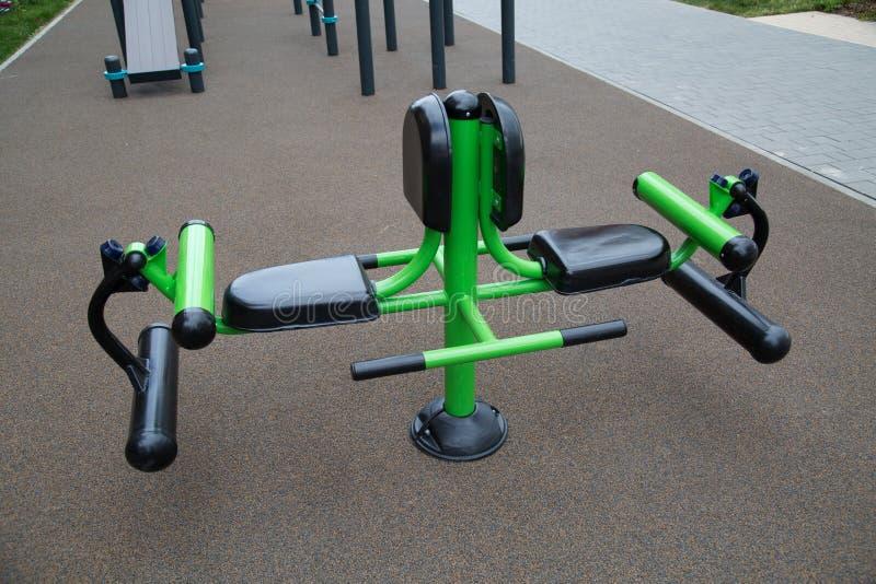 腿肌肉的力量教练员由金属制成在操场在城市户外 图库摄影