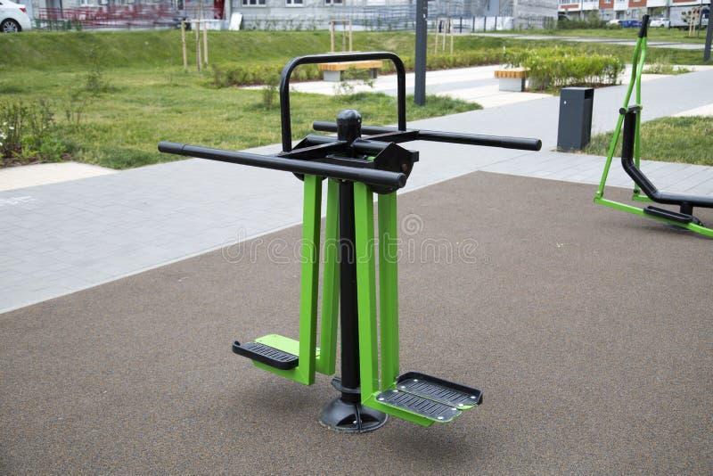 腿肌肉的力量教练员由金属制成在操场在城市户外 免版税库存照片