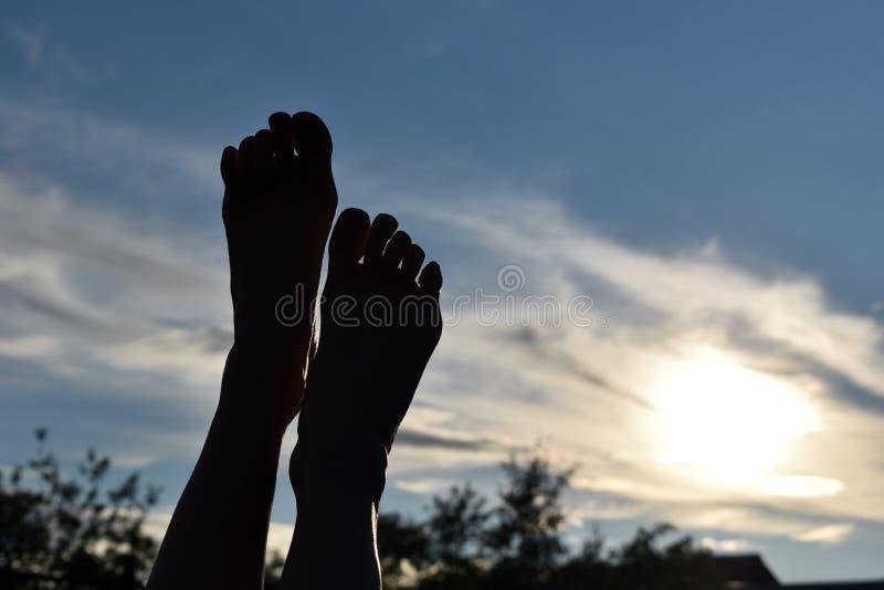 腿黑暗的剪影在日落的在天空 腿的脚被举对太阳 库存图片